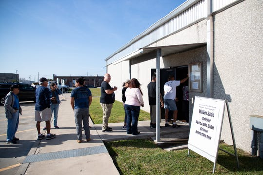 People Monday morning stand inline at the CCISD athletic office to buy tickets for the Miller vs. Veterans Memorial third round playoff game at Buc Stadium on Friday.