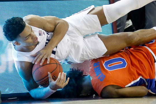 Xavier's Bryce Moore, on top, goes for a loose ball as he falls over Florida's Ques Glover in the first half of an NCAA college basketball game during the finals of the Charleston Classic Sunday, Nov. 24, 2019, in Charleston, S.C.