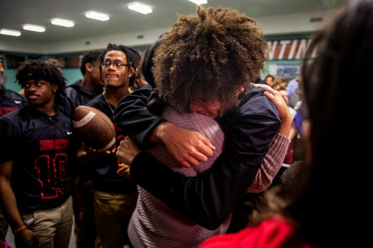 Dana Gendreau embraces Dominic Robinson, a Hughes senior and outside linebacker, after Good Morning America surprised Gendreau at Hughes STEM High School in Clifton on Monday, November 25, 2019.