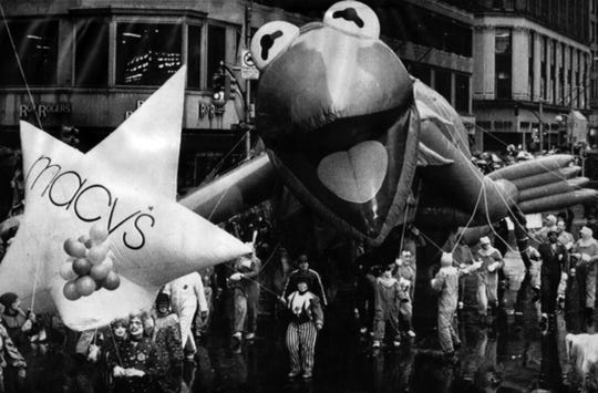 NOVEMBER 28, 1985: Kermit the Frog, leaking helium during the Macy's Thanksgiving Parade in New York City, shambles along the pavement as rain-soaked parade workers struggle to keep him moving.