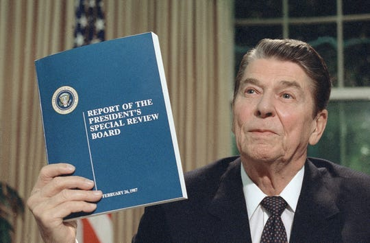 """President Ronald Reagan holds up a copy of the Tower Commission report on the Iran-Contra affair, while posing for photographers after his nationally televised speech from the Oval Office in Washington, Aug. 13, 1987. Reagan said he was """"mad as a hornet"""" about damage to his administration from the Iran-Contra affair."""