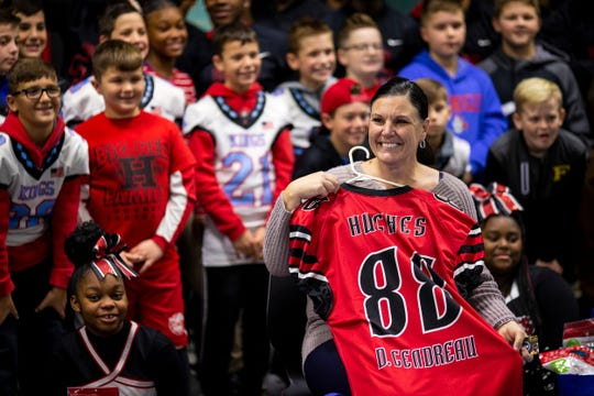 Hughes football coach Chris Mobley surprises Dana Gendreau with her own Big Red jersey, after Good Morning America surprised Gendreau at Hughes STEM High School in Clifton on Monday, November 25, 2019.