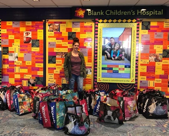 "Amber Hayes stands in the midst of several gift bags before handing them out at Blank Children's Hospital last year. Her family's ""Spreading Joy for Joe"" drive, in memory of her son Joseph Livingston, is now in its second year."