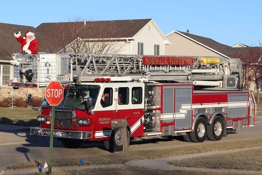 Tom Guthrie rides on a fire truck through Norwalk last year.