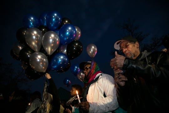 Members of the community come together during a vigil for fallen Detroit Police Officer Rasheen McClain outside of the 12th Precinct near Palmer Woods Monday Nov. 25, 2019.