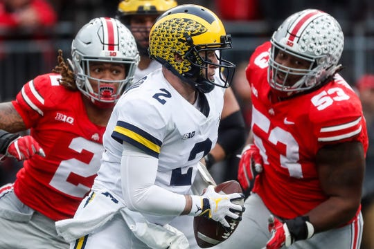 The Wolverines' Shea Patterson dodges the Buckeyes' Chase Young (2) in 2018 in Columbus.
