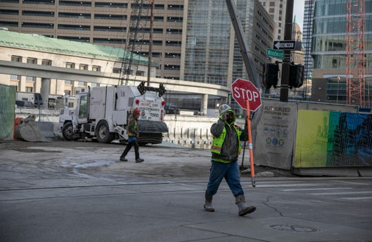 Workers prepare to stop traffic on Woodward Avenue in Detroit to make way for heavy construction vehicles leaving the Hudson's site last November.