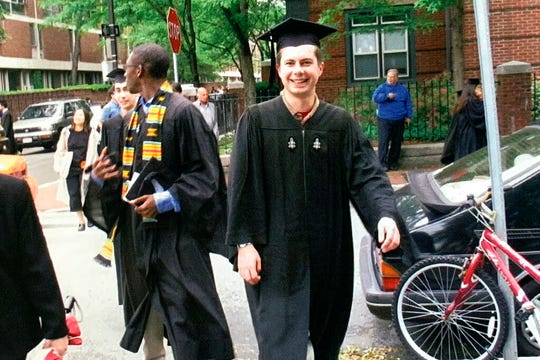 In this image provided by the Pete Buttigieg presidential campaign, Pete Buttigieg walks with his friend Uzo, left, to meet his parents before going to his house graduation at Leverett House at his Harvard graduation on June 10, 2004 in Cambridge, Mass.