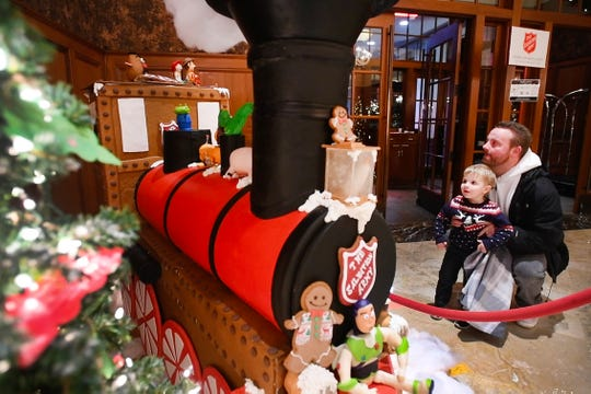 Scott Herz and son Bennett, 2, take in the gingerbread train at the Royal Park Hotel lobby in Rochester.