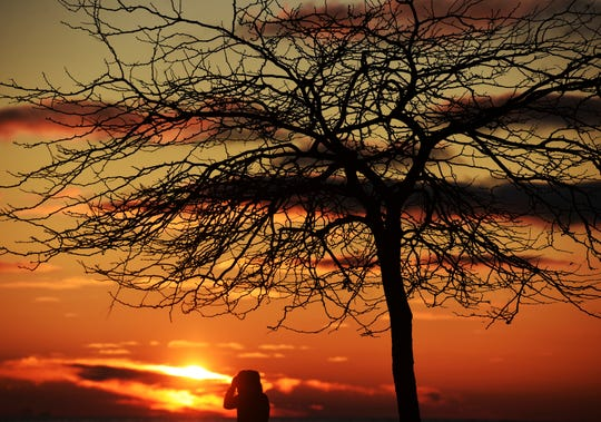A woman enjoys a crisp sunset walk along Silver Beach in St. Joseph, Mich.