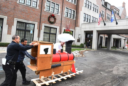 Royal Park pastry chef Mark Slessor, with help from Felix Colom and Julio Feliz, leads the train, made with the help of Salvation Army of Metro Detroit, toward the lobby.