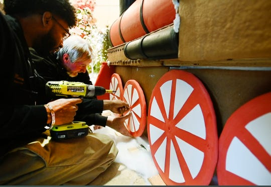 Royal Park Hotel engineers Marcus Jordan and Bill Klier attach the wheels on the gingerbread and fondant train.