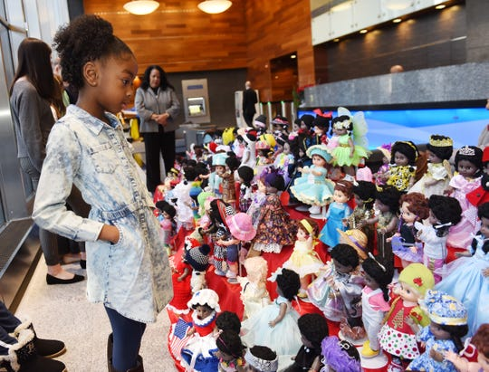 Judge Ava King, 6, of Canton Township, observes the dolls during the judging period of the Old Newsboys' Goodfellow Fund doll-dressing contest Monday at Comerica Bank in Detroit.