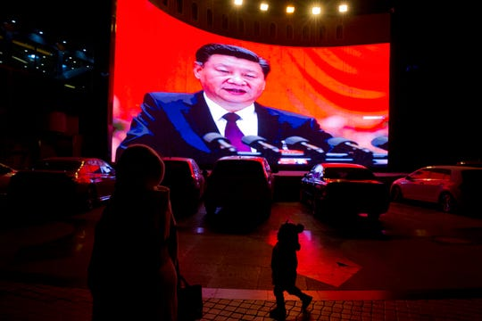 In this Dec. 3, 2018, file photo, a child walks past a large screen showing Chinese President Xi Jinping near a carpark in Kashgar, western China's Xinjiang region. Across the Xinjiang region, a growing number of internment camps have been built, where by some estimates 1 million Muslims have been detained, forced to give up their language and their religion and subjected to political indoctrination.