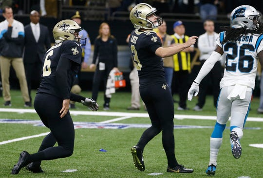 New Orleans Saints kicker Wil Lutz (3) looks up as he kicks the game-winning filed goal, during the second half. To the left is New Orleans Saints punter Thomas Morstead (6) and Carolina Panthers cornerback Donte Jackson (26), left.