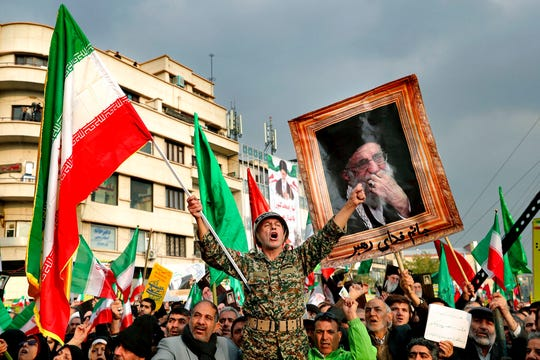 A demonstrator chants slogans while holding up an Iranian national flag during a pro-government rally denouncing last week's violent protests over a fuel price hike in Tehran, Iran, Monday, Nov. 25, 2019.