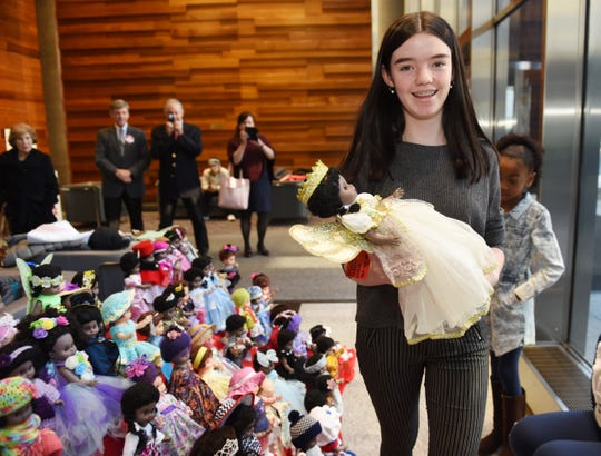 Natalie Stanczak,13, carries a doll to be judged in the final rounds of the Old Newsboys' Goodfellow Fund doll-dressing contest Monday at Comerica Bank in Detroit.