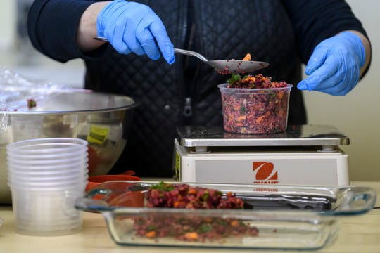 Peggy Pirro packages Holiday Quinoa salad which she will freeze for customers to buy at Common Ground Community Kitchen in Downtown Evansville, Monday morning, Nov. 25, 2019. Ingredients for the salad include carrots, beets, kale, sunflower seeds, pumpkin seeds, dried cranberries and a lemon vinaigrette.