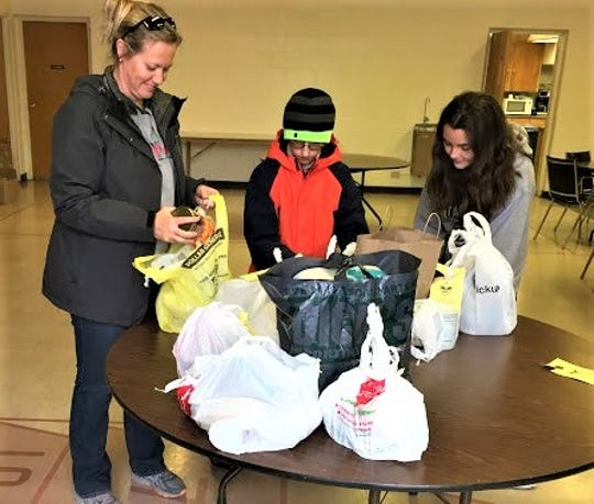 Shawna Shadoan counts donated items as Jack Barron and Allison Widmer add more donations to the table.