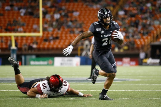 Hawaii running back Fred Holly runs past San Diego State defender Jonah Tavai for a touchdown Saturday night in the Rainbow Warriors' 14-11 win over San Diego State at Aloha Stadium in Honolulu. The victory clinched a berth in the Mountain West championship game for Hawaii as the West Division champion.