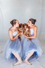 Two Canyon Concert Ballet dancers kiss a pair of hound mix puppies Nov. 23 in Fort Collins.