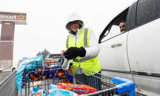 A Walmart employee grabs a bottle of water to give to a motorist stuck in the traffic in the parking lot in Timnath, Colo. on Monday, Nov. 25, 2019.