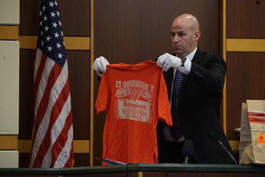 Jefferson County Detective Nick Schueneman shows the jury a shirt that was admitted into evidence in the trial for Mark Sievers, who is charged with first-degree murder and conspiracy to commit murder for the death of his wife Teresa Sievers, Monday, Nov. 25, 2019, at the Lee County Justice Center in Fort Myers.
