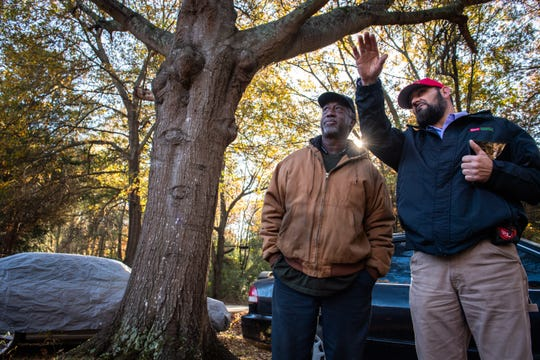 Bobby Hogan, an Army veteran who served from 1980-1992, talks with Richard Abernathy of Guy Roofing as workers install a new roof on Hogan's home Monday, November 25, 2019. The new roof was donated by Owens Corning.