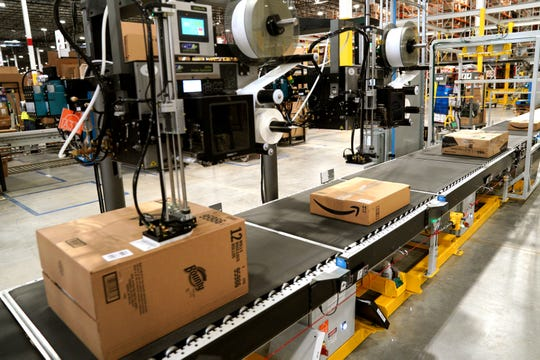 A machine applies shipping labels to packed orders at an Amazon fulfillment center May 3, 2018, in Aurora, Colorado.