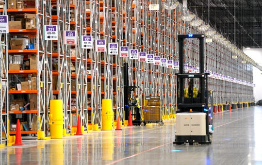 A worker drives a powered industrial truck at an Amazon fulfillment center. While the company instructs workers on the safe way to move their bodies and equipment, workers have said they have to break the safety rules to keep up with demanding quotas.