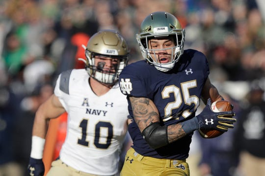 Notre Dame wide receiver Braden Lenzy (25) makes a touchdown reception against Navy safety Kevin Brennan (10) during the first half of an NCAA college football game, Saturday, Nov. 16, 2019, in South Bend, Ind. (AP Photo/Darron Cummings)