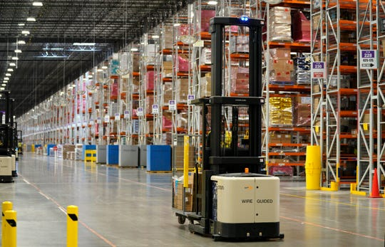A worker drives a powered industrial truck at an Amazon fulfillment center May 3, 2018, in Aurora, Colorado.