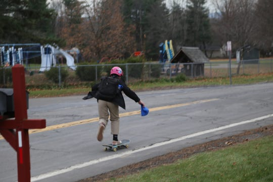 A Dewitt Middle School student rides a skateboard on Winthrop Drive.