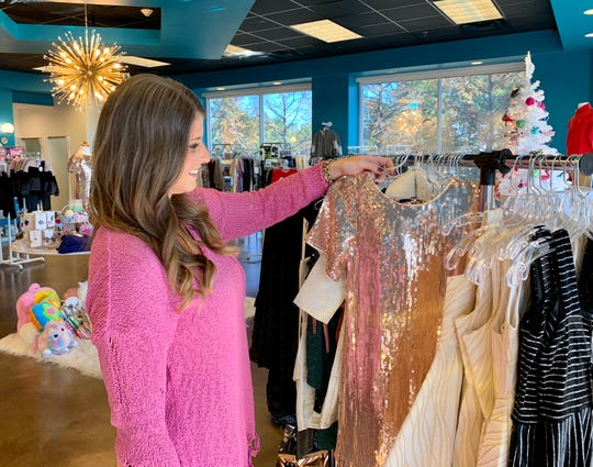 Livi James in Madison specializes in fashions for girls and boys in sizes 6-16, shoes from toddler size 11 to youth size 5, gifts and accessories. Fran Fowler, owner of Livi James, checks out a sparkling party dress that is for sale at the boutique.