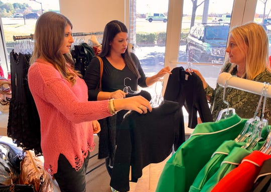 Fran Fowler, left, owner of Livi James in Madison, and Kellie Bosarge, an employee at Livi James, show options for jackets to Lauren Grissom of Madison.