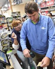 Matt Jones of the Mississippi Lottery assits RaceWay employee Arnice Montgomery in scanning one of the first scratch off lottery tickets sold on Monday, Nov. 25, 2019 at the RaceWay location on Mississippi Highway 18 in south Jackson.