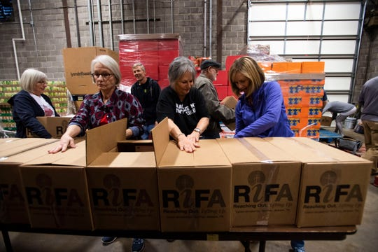 Volunteer members, help pack the RIFA boxes stuffed with meals to provide at the senior center in Jackson, Tenn., Wednesday, Nov. 20, 2019.