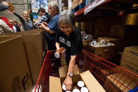 Joyce Dunlap picks up pasta sauce to pass off to her husband Mike Dunlap at RIFA's warehouse to help pack the RIFA boxes with meals to provide at the senior center in Jackson, Tenn., Wednesday, Nov. 20, 2019.