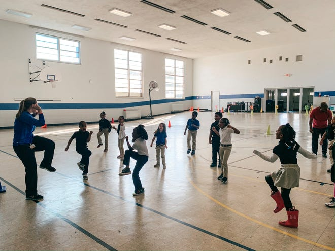 Alexander Elementary P.E. teacher Maggie Chandler models how to do an exercise of PowerUp Your School, a fitness program that aligns with academic standards.