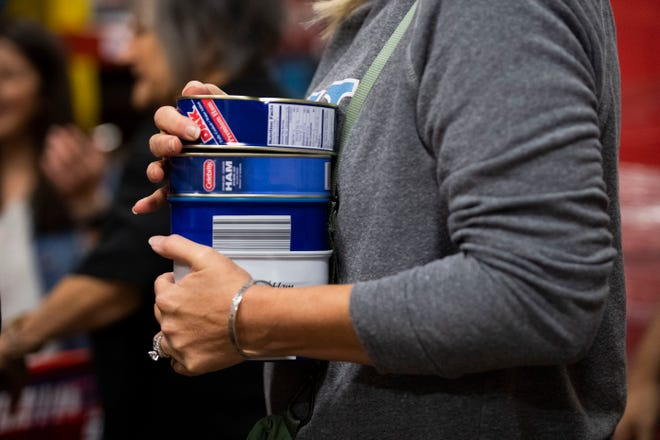 Volunteer member Danna Jett, holds canned ham to put inside the RIFA boxes to provide meals for the senior center in Jackson, Tenn., Wednesday, Nov. 20, 2019.
