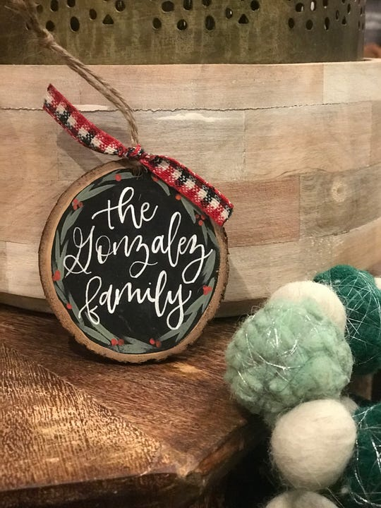 Erica Price, owner of Flourish + Jot, can hand-letter family holiday ornaments. She accepts orders via her website and at craft markets.