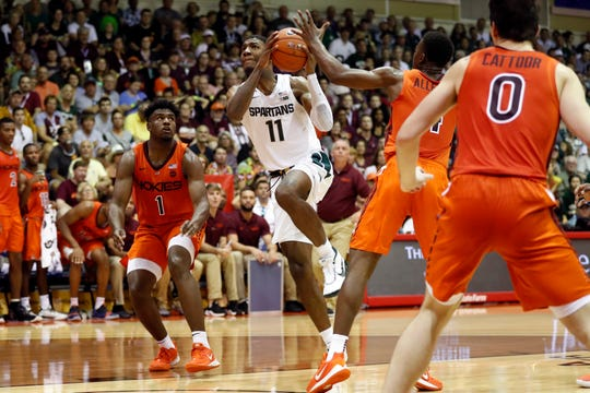 Michigan State forward Aaron Henry (11) gets through the Virginia Tech defense during the first half of an NCAA college basketball game Monday, Nov. 25, 2019, in Lahaina, Hawaii. (AP Photo/Marco Garcia)