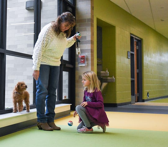 Molly Tobin, right, a first-grader at Donley Elementary School in East Lansing tries to meet the school's new 'mascot,' a four-month-old Miniature Goldendoodle whom students will name next week.  The therapy dog in training will stay with handler Kathy Wilson, middle, a fourth-grade teacher at the school.