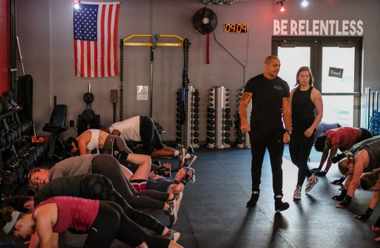 Brian Daniels and Leah Traciak-Zenker, owners of EmPOWer gym on East Michigan Avenue, in Lansing work with participants in their class on Saturday, Nov. 23, 2019.