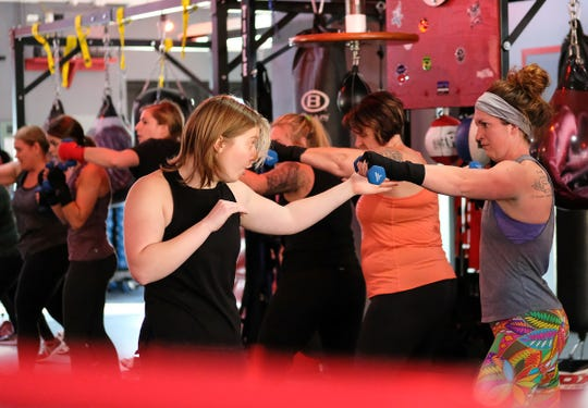 Leah Traciak-Zenker, left, co-owner of EmPOWer gym instructs students during a long warm-up session on Saturday, Nov. 23, 2019.