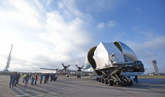 The Orion space capsule is slowly moved out of the Super Guppy airplane Monday and later loaded on to a oversized flatbed trailer for transport on Tuesday to NASA's Plum Brook Station in Sandusky.