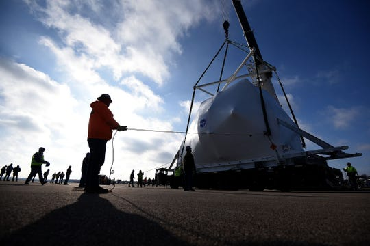 Workers guide the the Orion space capsule towards a flatbed trailer for transport on Tuesday to NASA's Plum Brook Station in Sandusky.