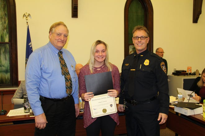 Village of Pewaukee President Jeff Knutson (left) and Pewaukee Police Chief Tim Heier present Pewaukee Beach lifeguard Ashley Zlotocha with the Meritorious Award. Zlotocha, along with lifeguards Alec Lanza and Lauren Launer, displayed heroic actions when they helped protect three children from a suspicious man at the beach.