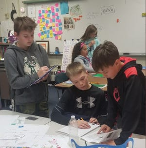 """Frank Lloyd Wright Intermediate School students (foreground, from left) Austin Minessale, Peyton Ryback and Simon Pratt along with Angelica Henderson and Alexis Gross (standing) become """"travel agents"""" as they prepare flyers and posters for a Deeper Learning project about other countries in the 2018-19 school year."""