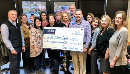 At Arvest Bank's donation presentation at The CALL of Baxter County were (back row, left to right) Mike Willard, Melissa Brown, Jessica Woods, Nancy Bloomquist, Kyle Davidson, Glenna Cruz, (front row, left to right) Aubrey Wilson, , Sandy LaBahn, Sally Gilbert, Zack Lashley, Adrienne Blackwell, Ashley Hambelton, and Dawn Cotter.